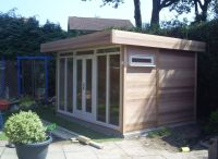 Clad with cedar, with natural stone double doors and sidelights. High level windows are also included.