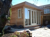 Contemporary Design clad in cedar, with cream double doors and sidelights.