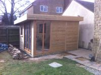 3.8m x 3.6m Cedar Garden Room with a trifold door - and a sidelight to the side.