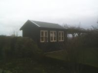 12 x 8 Traditional office with black metal roofing. Stained black with cream doors and windows. Taken on a misty day!