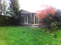 Large featheredge garden office with contemporary doors and windows. The covered veranda completes the look.