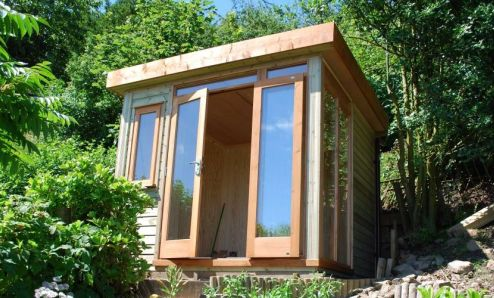 Squeezed onto a small rocky ledge and set high up in the garden, this insulated Garden Room offers spectacular views over the valley below
